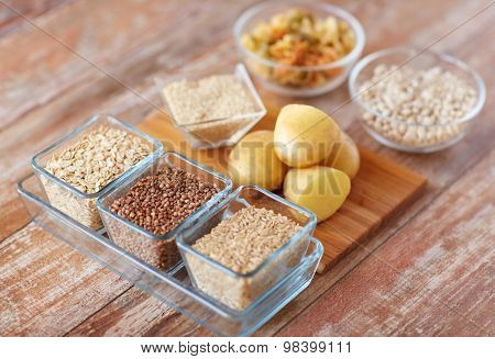 diet, cooking, culinary and carbohydrate food concept - close up of grain, cereals in glass bowls and potatoes on table