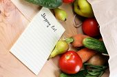 Heap of fruits and vegetables with shopping list on table close up poster