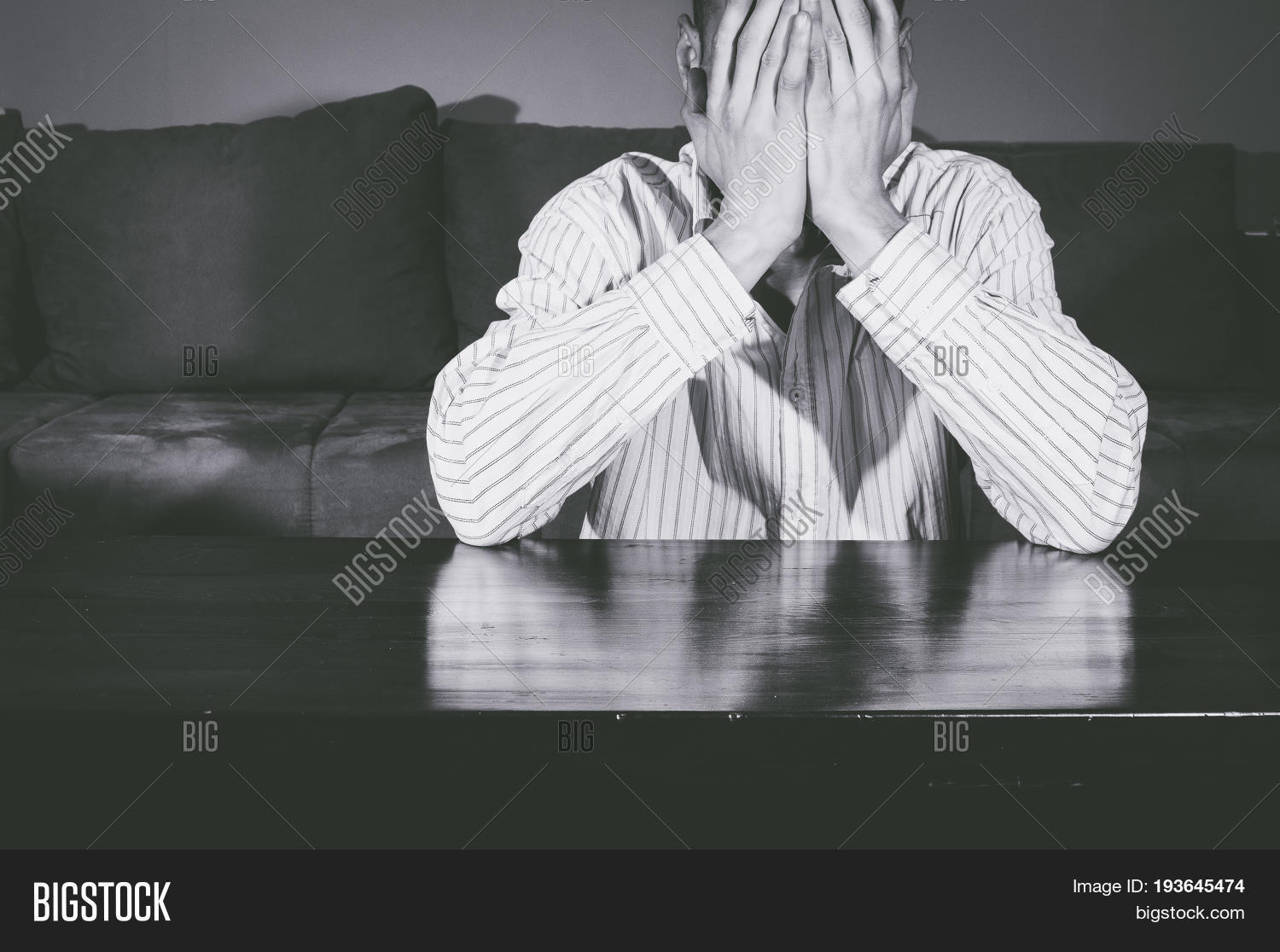 Depression depressed man cover his face with his hands and cry black and white
