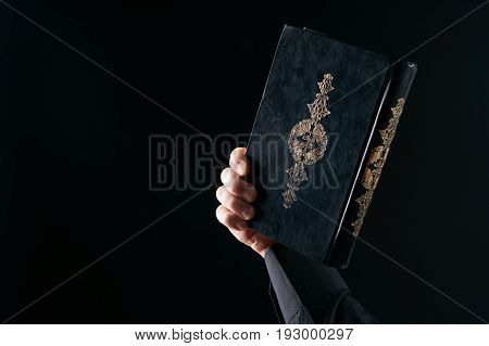 Muslim man hands holding the Koran/ Quran Islamic holy book. Black background with copy space.