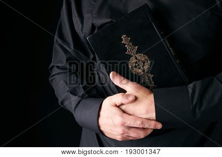 Holy Koran/Quran in Man's hand - holy book of Muslims. Black background with copy space . Public item of all muslims
