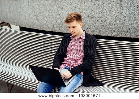 Stylish young man in jacket and jeans sitting on the bench and typing on laptop computer outdoors. Technology and communication concept