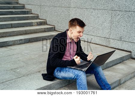 Happy man with laptop computer. I did it! Young man looking at computer monitor on his knees and shout. Happy man completed task and triumphing with hands clenched into fist outdoors