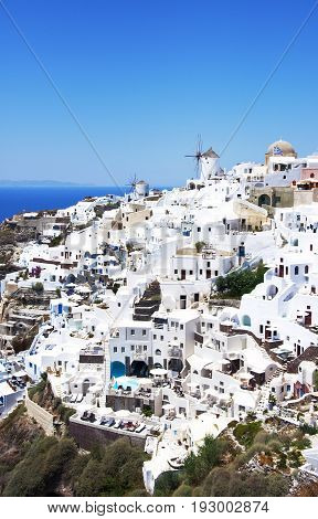 View of the village of Oia, Santorini, Greece. Traditional Greek architecture, white houses, the Aegean Sea, the caldera.