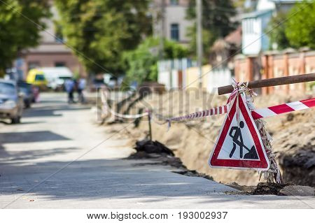 Construction roadwork on street in city. Red safety sign warns about roadworks. Be careful danger on your way
