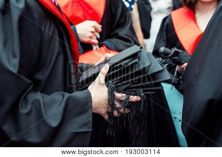 Man holding a lot of mortar boards in focus on a summer graduation day in a Univercity