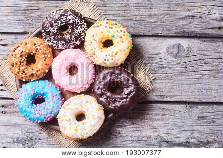 assorted donuts with chocolate frosted pink glazed and sprinkles . Top view . Space for text