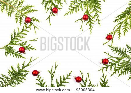 Wide arch shaped Christmas border on white background composed of fresh fir branches and ornaments red and silver balls
