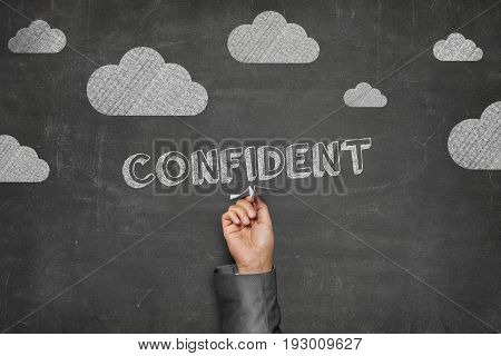 Cropped image of businessman holding paper plane under confident text and clouds on blackboard