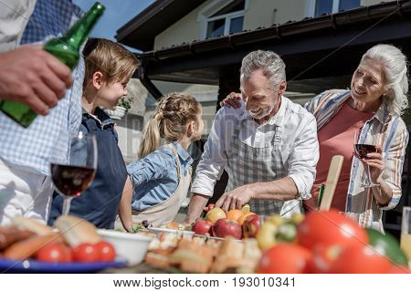 happy grandparents and grandchildren preparing food on picnic outdoors