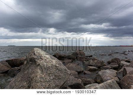 rocks boulders in water coast Gulf of Finland the rain clouds in the sky