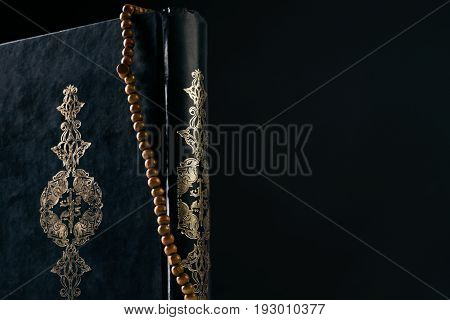 Prayer beads rosary on Koran/ Quran ( holy book of Muslims ) isolated on black background with copy space. Close-up