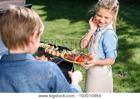 Pre-adolescent Kids Preparing Meat And Vegetables On Barbecue Grill Outdoors