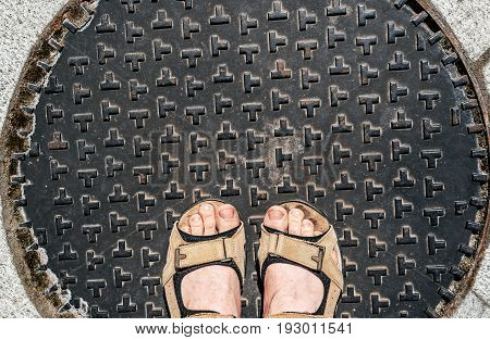Man wear brown shoes standing on manhole cover at footpath. Pair of feet on manhole cover