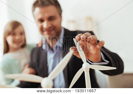 Progressive technologies. Nice optimistic passionate man working on new ideas while developing an energy friendly turbine and explaining how it working to his child