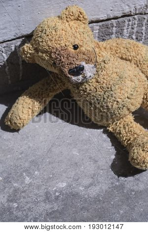 Old plush toy on the concrete floor. Best use as a book cover or poster.