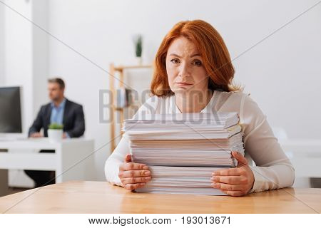 Too many duties. Tired committed young woman sitting at the office and holding a pile of papers she needing working on today