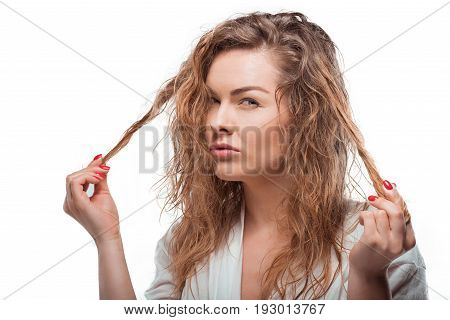 Skeptical Blonde Woman Touching Her Hair And Looking At Camera Isolated On White