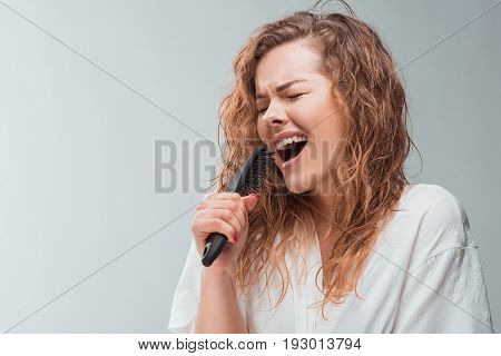 Emotional Blonde Woman Singing With Hair Comb, Isolated On Grey