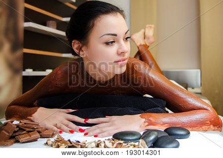 Chocolate body wrapping. SPA. Young beautiful girl lies on massage table. Female body covered with cosmetic chocolate.