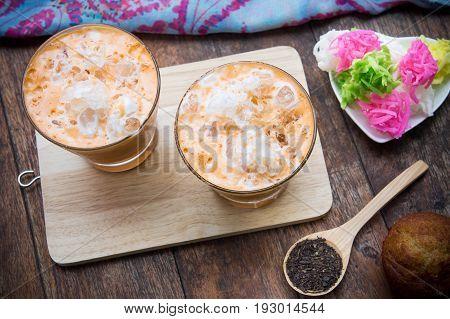 thai tea milkshake beverage thailand style and muffin cupcake dessert on wood table