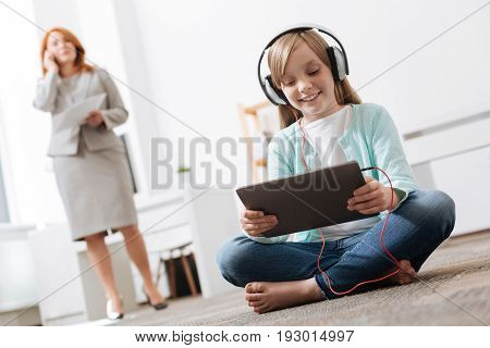 Technological kid. Pretty adventurous savvy girl going to work with her mom while playing with her gadget as her mother actively working