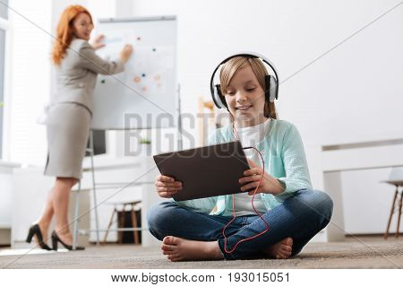 Inspired lady. Cute productive savvy girl sitting on the floor and playing with her tablet while her mom watching her from behind