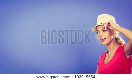 Technology photography modern devices concept. Tourist woman in sun hat taking pictures with her smartphone on selfie stick. Studio shot on blue background