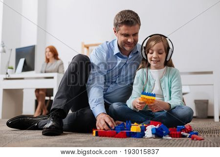 Little architect. Charismatic attentive loving father entertaining his child while brining her to the office with him and making sure she not bored