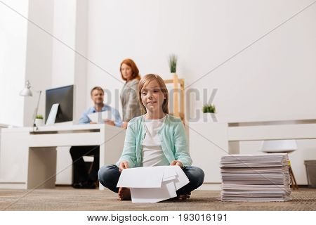Calmness of the workplace. Cute sincere hilarious girl sitting on the floor in the office and thinking about entertaining herself a little