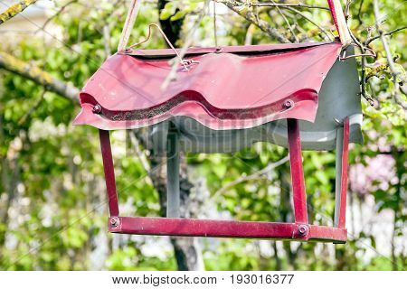 Metal red feeder for birds. Green background.