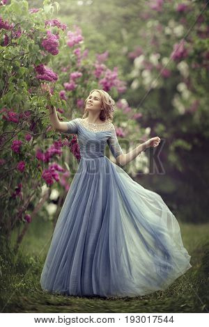Beautiful young girl in a blue dress as a cinderella is walking in the garden. Admiring the flowers of lilac.