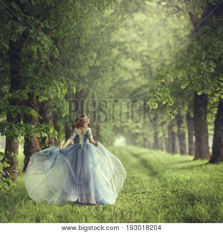Back view of standing young woman in blue dress. Runs like Cinderella.