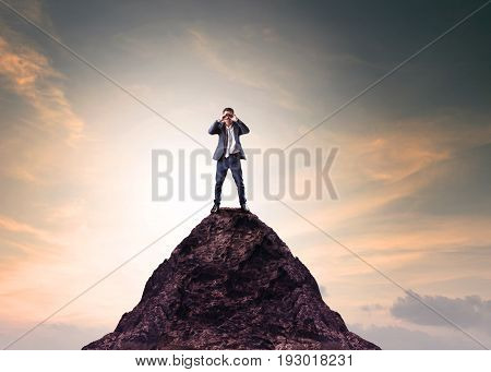 business man and binocular lens standing on top of mountain and looking through for serching