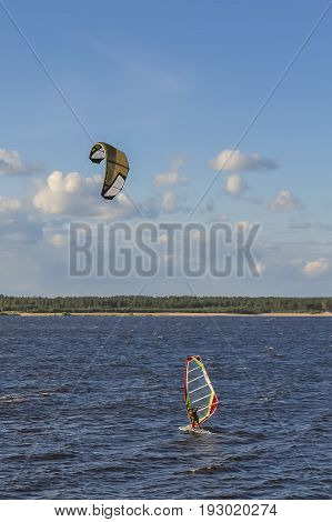 Kiteboarding (kitesurfing) is a water sport. A man is engaged in kiteboarding on the river.