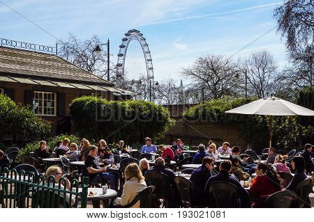 LONDON, ENGLAND, UK - APRIL 24 2017 : unidentified people relax in the park lunch break. Is widespread eating lunch in one of the city parks during the beautiful days