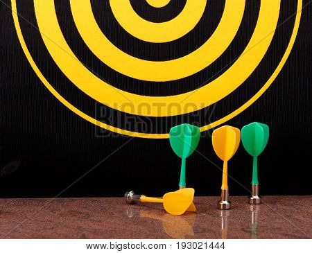 Magnetic dart arrows on granite surface and yellow dart board background.