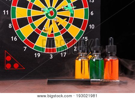 Electronic cigarette and bottles with vape liquid within vapor on dart board background with magnetic arrows