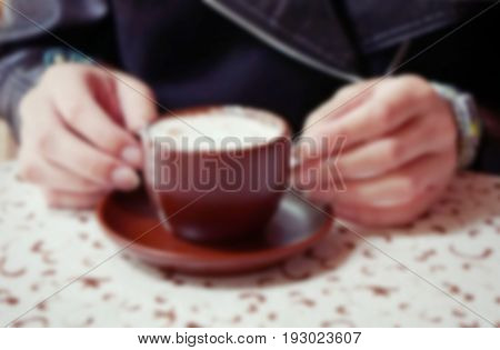 Female hands holding a cup of caffe mocha; blurred background