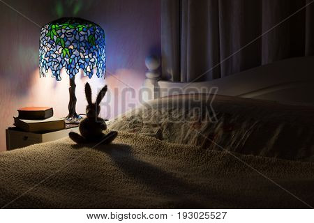 Bedroom interior at night. A dark room illuminated by a decorative stained glass lamp silhouetting a toy rabbit. Story time at bedtime concept.