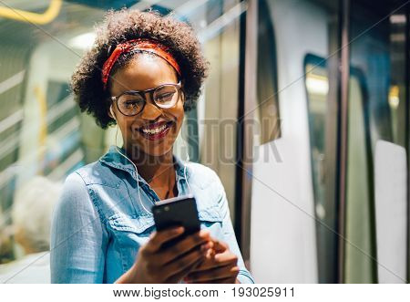 Smiling Young African Woman Listening To Music On Her Commute