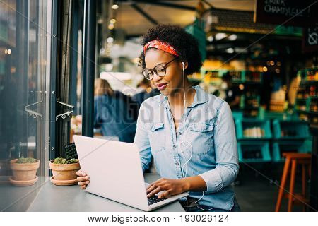 Focused Young African Woman Working Online In A Cafe