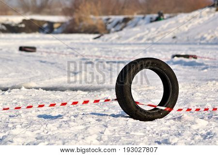 Black rubber tyre marks the edge of a winter snowy off-road racetrack