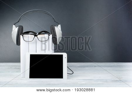 Audiobook on back background. Headphones put over stack of books, empty cover, copy space for ad text. Distance education, e-learning concept. Tablet PC