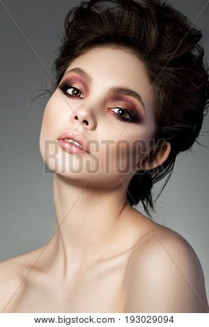 Beauty portrait of young woman with modern smokey eyes makeup. Perfect skin and fashion makeup smokey eyes. Studio shot. Sensuality passion trendy luxurious makeup and cosmetology concept.