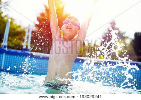 Happy little boy jumping in swimming pool hands up in the air