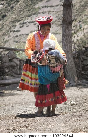 Native peruvian woman smilling and playing with her kids October 21 2012 - Patachancha Cuzco Peru