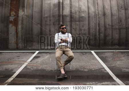 Fashionable Handsome Man In Sunglasses And Suspenders Sitting On Parking Place