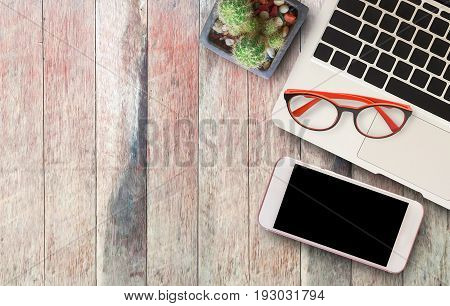 Laptop computersmart phonered glasses and cactus on wooden table background. office desk and business concept.top view with copy space