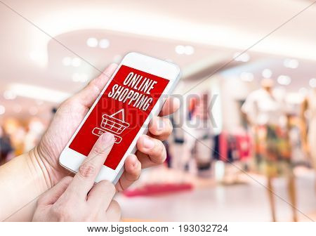 Hand Holding Mobile Phone With Online Shopping Word With Blurred Store Background With Bokeh Light ,